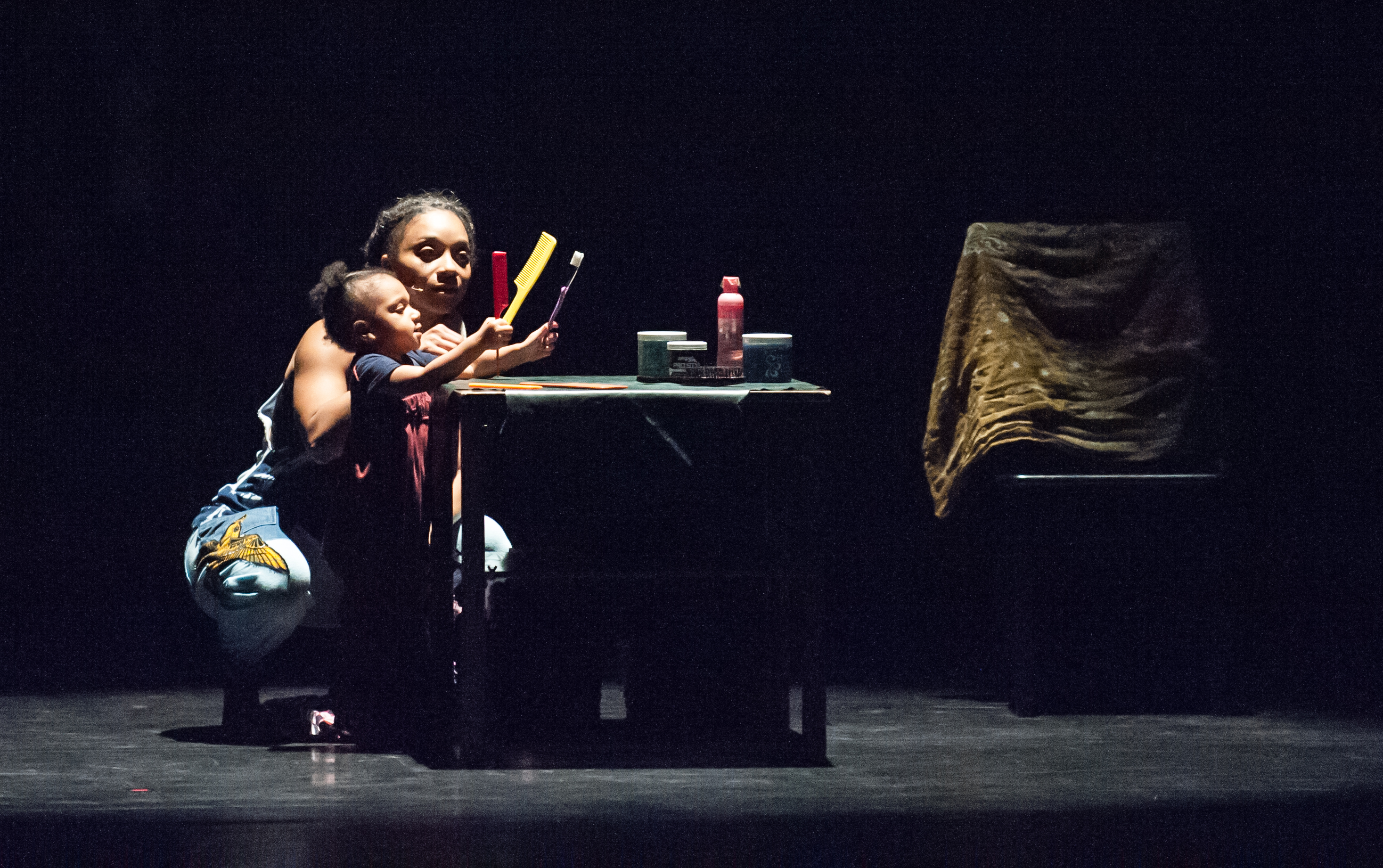 An adult and child performer in a scene from Urban Bush Women's Hair and Other Stories.